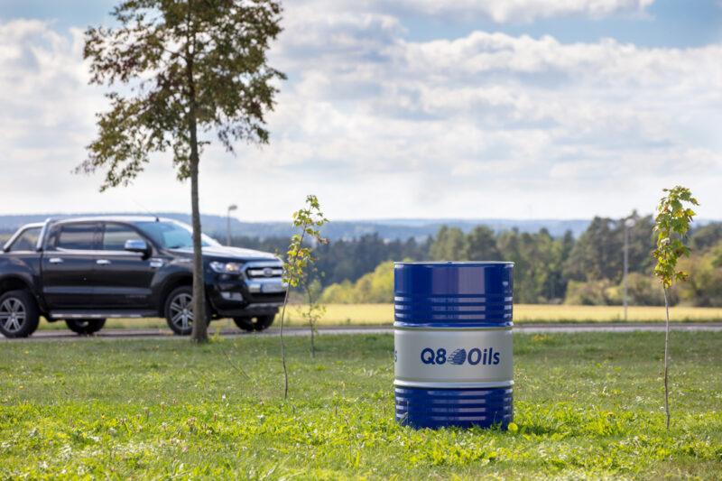 Q8 Oils Fass steht auf einer Wiese mit PickUp Truck im Hintergrund